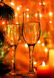 New Year's Eve wine. New Years and Christmas Eve celebration background with an elegant arrangement with flutes and bottle of champagne and burning candles Royalty Free Stock Photo