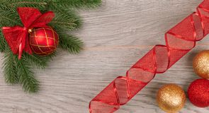 New Year`s fir branch with red ribbon dark background with yellow and red balls stock photography