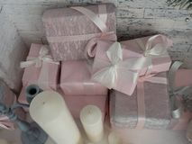 New Year`s gift in boxes of light pink tones and festive candles. Royalty Free Stock Photos