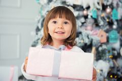 New Year`s gift, emotions of happiness and joy. Little smiling girl gives a gift. Close-up. In the interior. New Year`s gift, emotions of happiness and joy Royalty Free Stock Photos
