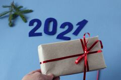 New year`s gift in hand against the background of the figures of the coming year-2021, close - up-the concept of pleasant new yea