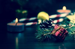 New Year`s gift in red packing with a gold bow near the paw of the Christmas tree close-up macro on a wooden table. Royalty Free Stock Photos