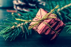 New Year`s gift in red packing with a gold bow near the paw of the Christmas tree close-up macro on a wooden table. Vintage, grunge old retro style Stock Images