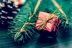 New Year`s gift in red packing with a gold bow near the paw of the Christmas tree close-up macro on a wooden table. Vintage, grunge old retro style Stock Photo