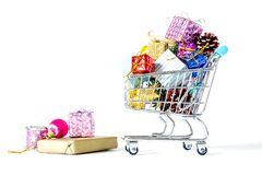 New Year`s gifts in a shopping trolley close-up isolated. On a white background. A shopping cart full of Christmas gifts isolated on white background Royalty Free Stock Image
