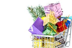 New Year`s gifts in a shopping trolley close-up isolated. On a white background. A shopping cart full of Christmas gifts isolated on white background Royalty Free Stock Photography