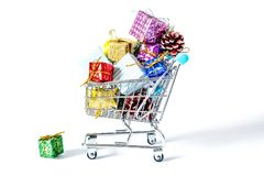New Year`s gifts in a shopping trolley close-up isolated. On a white background. A shopping cart full of Christmas gifts isolated on white background Royalty Free Stock Photo