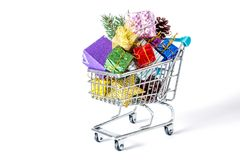 New Year`s gifts in a shopping trolley close-up isolated. On a white background. A shopping cart full of Christmas gifts isolated on white background Stock Photography
