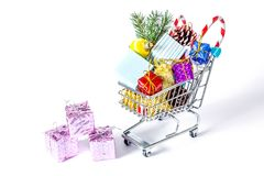 New Year`s gifts in a shopping trolley close-up isolated Royalty Free Stock Photos