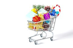 New Year`s gifts in a shopping trolley close-up isolated. On a white background. A shopping cart full of Christmas gifts isolated on white background Royalty Free Stock Photos