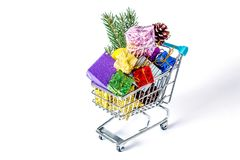 New Year`s gifts in a shopping trolley close-up. On a white background. A shopping cart full of Christmas gifts isolated on white background Stock Photo