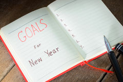 New Year's goals with notebook and pen. New Year's goals with with notebook and pen. New Year's goals are resolutions or promises that people make for the New Stock Photos