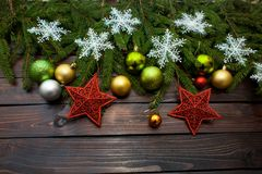 New Year`s green, yellow and silver balls together with red stars and with live fir branches on a wooden background with white sn Stock Image