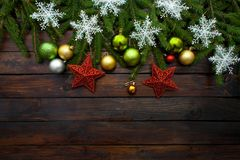 New Year`s green, yellow and silver balls together with red stars and with live fir branches on a wooden background with white sn. Owflakes. Top view royalty free stock images