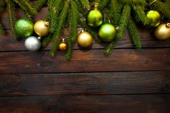 New Year`s greens, yellow and silver balls with live fir branches on a wooden background. Top view.  stock photography