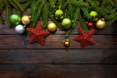 New Year`s greens, yellow and silver balls together with red stars and with live fir branches on a wooden background. Top view.  royalty free stock photo