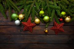 New Year`s greens, yellow and silver balls together with red stars and with live fir branches on a wooden background. Top view.  stock photos