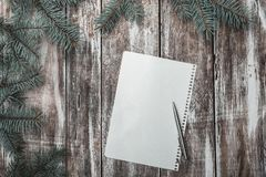 New year`s greeting card on old wood background, with green fir branches, and white sheet for a congratulatory message. New year`s greeting card on old wood Stock Images