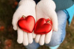 New Year& x27;s heart toys. A girl in white gloves holds toys on a Christmas tree in the shape of red hearts Stock Photos