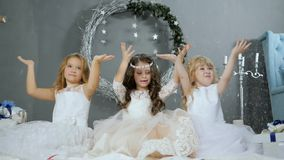 New Year`s holidays, children in white dresses with raised hands catch artificial snow in studio. New Year`s holidays, children in white dresses with raised stock footage