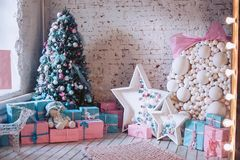 New Year`s interior. Christmas tree, decorative ornaments, gifts and toys under it. Luxurious, bright, beautiful home interiors. New Year`s interior. Christmas Stock Images