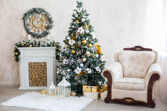 New Year's interior with a fireplace, a fur-tree and candles Royalty Free Stock Images