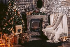 New Year`s interior with a warm fireplace, a Christmas tree and decorative elements in dark colors. New Year`s interior with a warm fireplace, a Christmas tree Stock Photo