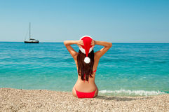 New Year's meditation on the beach. Girl on the beach in a Christmas hat Royalty Free Stock Image