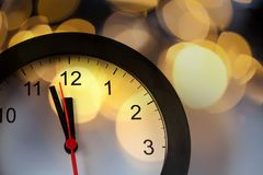 New Year& x27;s at midnight - clock at twelve o& x27;clock with holiday li Royalty Free Stock Image