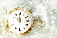 New Year's at midnight and holiday lights. New Year's at midnight - Old golden clock with stars and snowflakes Stock Image