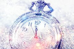 Twelve o`clock - new year`s eve. New Year`s at midnight - Old clock with stars snowflakes and holiday lights Stock Image