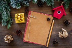 New year`s mockup. Sheet of paper near christmas toys and present, spruce branches on dark wooden background top view Royalty Free Stock Photos