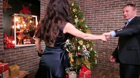 New Year`s party near the Christmas tree, family is beautiful dances in the house, romantic moment for a husband and. Wife, loving couple dancing at a party stock footage