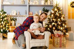 New Year`s picture of dad hugging son sitting on chair Stock Photos