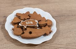 New Year`s piggy for good luck from Christmas gingerbread. Plate with Christmas cookies and hand-decorated pig on a wood background Stock Photo