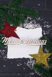 New Year`s or Christmas postcard. New Year`s postcard. An empty sheet of paper with snow, a multi-colored toy stars and a Christmas tree, flat lay Merry Stock Images