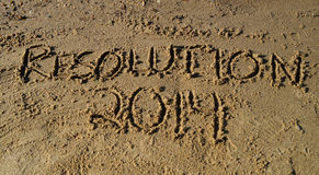 New Years Resolution 2014 in Beach Sand. The words resolution 2014 written in sand on the beach stock images