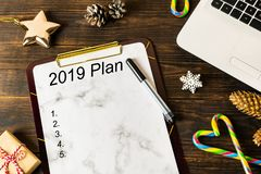New year`s resolutions, goals, plans and laptop with snowflakes, gold star, candy cane, pine cones on wooden background royalty free stock photography