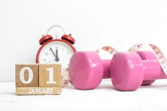 New Year's resolutions to work out, healthy lifestyle and diet c. Oncept. Pink dumbbells, alarm clock, and measuring tape with block calendar for January stock image