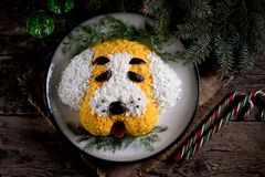 New Year`s Salad `Dog` for the celebration of 2018 - the year of the Yellow Dog. Salad of smoked chicken, boiled potatoes, soft ch Royalty Free Stock Image