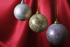 New Year's spheres on a red background. Three New Year's spheres hang on a red background Stock Images