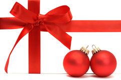 New Year's still-life. Red gift bow with ribbon and two red christmas balls isolated on white background Stock Photography