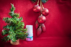 New Year`s still-life. In the foreground there is a Christmas tree, behind it there is a white candle. In the background, red Christmas decorations, cones and stock photo
