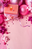 New Year's still-life in pink tones (top view). New Year's still-life with a candle and matte spheres in pink tones Royalty Free Stock Images