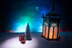 New Year's still-life postcard red lamp candle wax-boxes gift-box Christmas tree light bulbs lights wooden background snow. Christmas lantern on snow with gifts royalty free stock photos