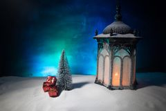 New Year's still-life postcard red lamp candle wax-boxes gift-box Christmas tree light bulbs lights wooden background snow. Christmas lantern on snow with gifts royalty free stock image