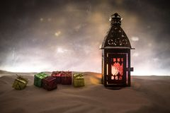 New Year's still-life postcard red lamp candle wax-boxes gift-box Christmas tree light bulbs lights wooden background snow. Christmas lantern on snow with gifts stock images