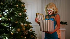 New Year's surprise box with a gift in a beautiful package, opens happy girl standing near the Christmas tree on party stock video