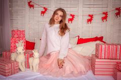 A bright girl in a sweater and a skirt is waiting for the New Year`s miracle. New Year`s themed shooting of the girl in anticipation of the New Year`s miracle Royalty Free Stock Photography