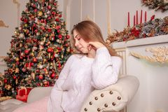 A bright girl in a sweater and a skirt is waiting for the New Year`s miracle. New Year`s themed shooting of the girl in anticipation of the New Year`s miracle Stock Photography